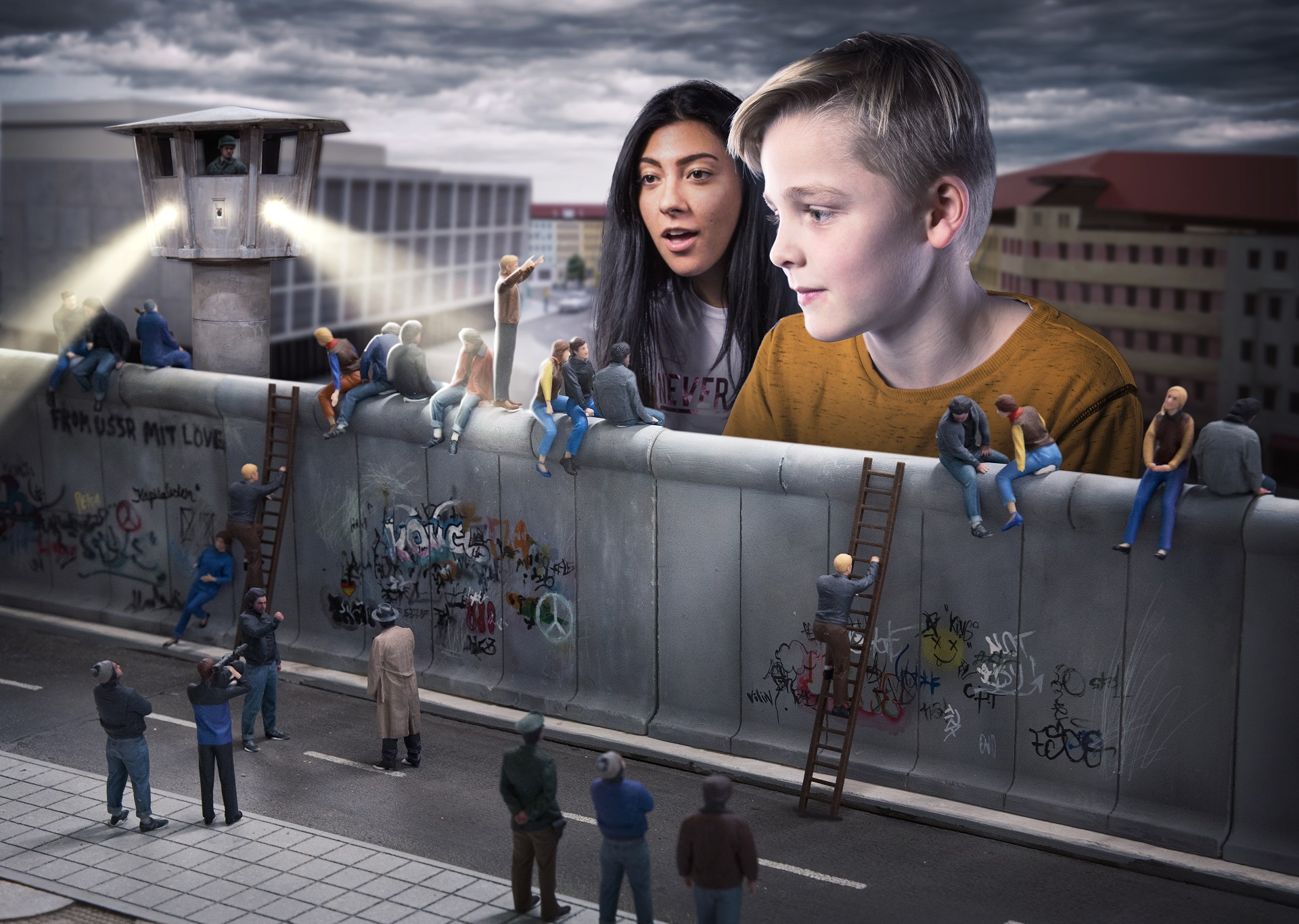 a boy and a girl watch the reconstruction of the Berlin wall with graffiti at Little BIG City Berlin