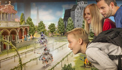 a kid with his family watches a miniature knights' competition at Little BIG City Berlin