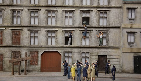 Miniature reconstruction of a woman throwing herself out the window to escape to West Berlin at Little BIG City Berlin
